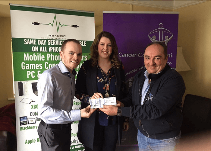 Phil from Cancer Connect NI and Kevin from TechDOC Repairs present our competition winner Donna Beacom with 2 tickets to see Ed Sheeran in Dublin.